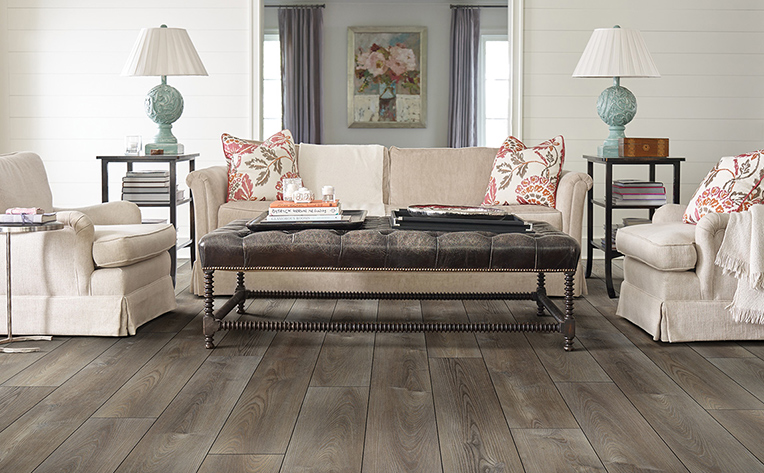 Beach inspired living room with distressed light brown luxury vinyl plank floors